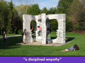 "People climbing through a giant book sculpture; slide text (in quotes): ""a disciplined empathy"""