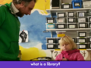 "Kid and grownup in front of shelves containing bins; slide text, ""what is a library?"""