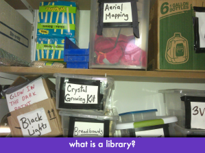 "closeup of bins on shelves; slide text: ""what is a library?"""